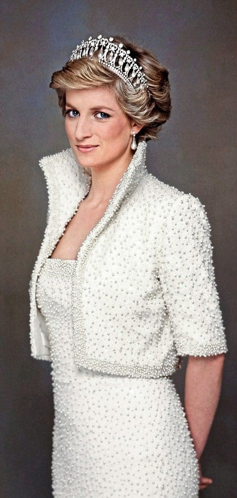 Princess Diana, a white woman with blonde hair, wearing a white dress and cropped high-collar blazer covered in pearls. She is wearing a diamond tiara and smiling into the camera. Via Getty Images.
