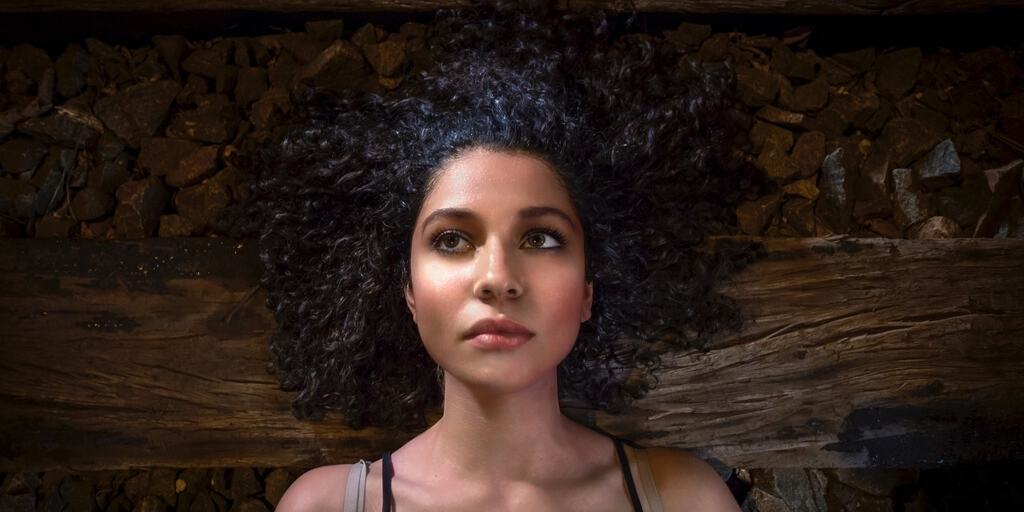 [image description: a girl wearing a black tank top with curly hair is lying on a hardwood floor looking thoughtful] by actionvance via Unsplash