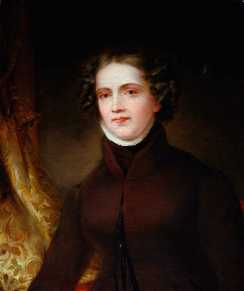A portrait of Anne Lister - a white women with short brown hair and wearing a dark red jacket