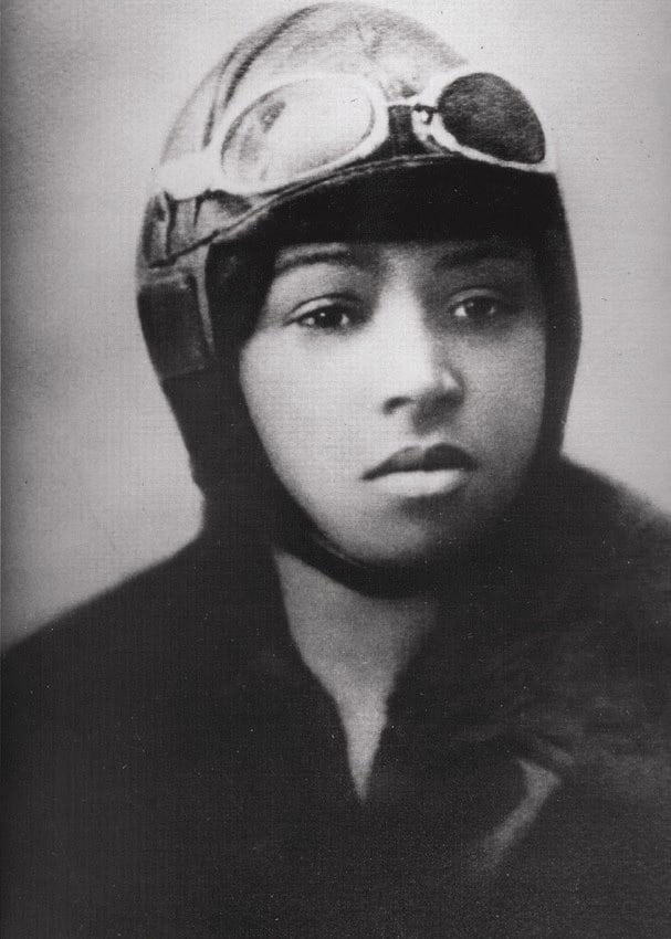 A black and white photograph of Bessie Coleman wearing flying goggles, hat and jacket
