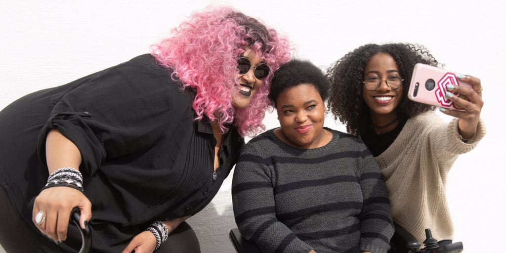 Three black women pose against a white background as they huddle in for a selfie. The woman on the right is wearing glasses and holding up her phone, the one in the middle is seated in a wheelchair and wears a coy smile, and the one on the left has neon pink hair and a cane in hand.