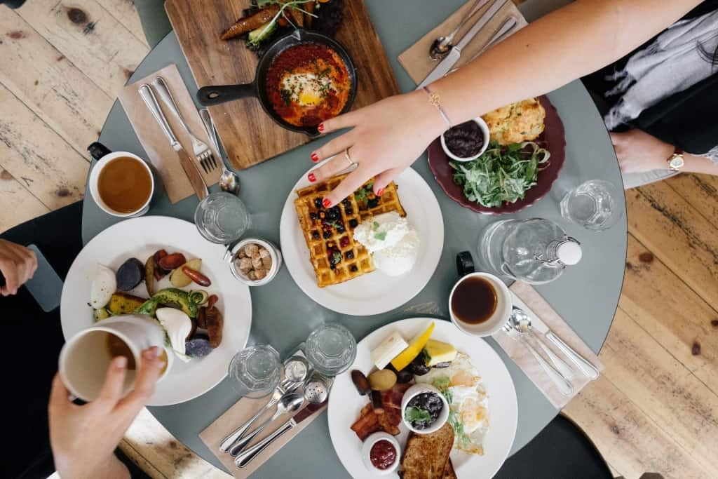 There is a grey table laden with different brunch foods like French toast and hands grabbing that food.