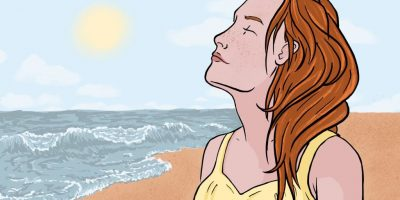 A digital image depicting a woman with red hair and pale skin at the beach. She has her hair pushed back, eyes closed and her face is tilted towards the sun. She is shown from the shoulders up, wearing a yellow swimsuit, with the sand and the ocean behind her.