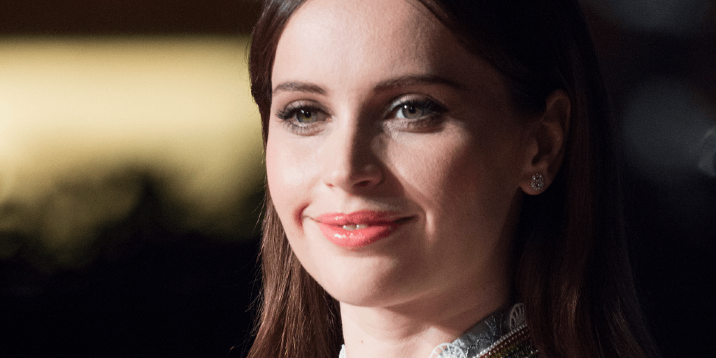 Felicity Jones - a white, brunette actress from Birmingham - is coyly smiling.
