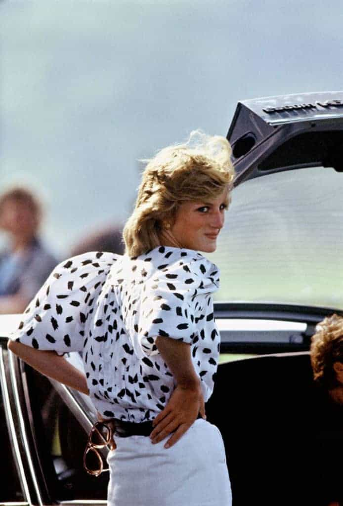 Princess Diana, a white woman with blonde hair, is wearing white jeans with a white blouse with black polka dots. She is soft smiling away from the camera. Via Getty Images.