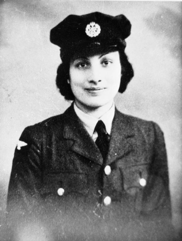 A black and white photograph of Noor Inayat Khan - an Indian woman with short black hair wearing dark British Air Force uniform