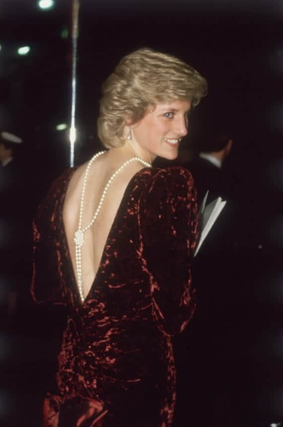 Princess Diana, a white woman with blonde hair, smiling into the distance while wearing a plum velvet dress with a string of knotted pearls in the back. Via Getty Images.