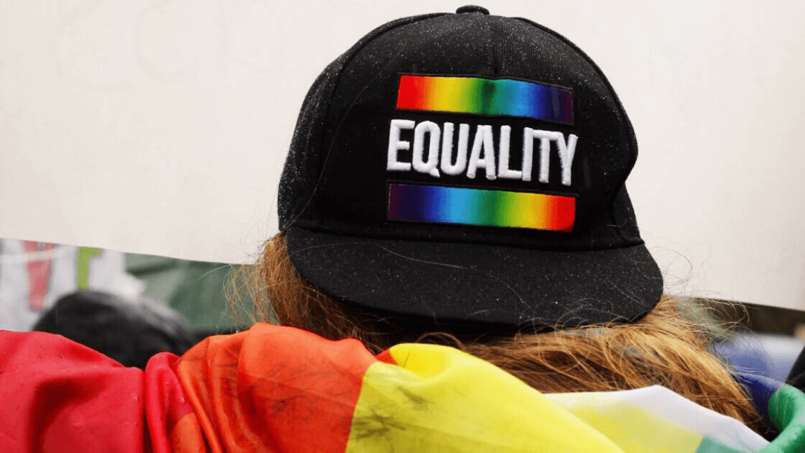 "A person is wearing a black cap with the word ""Equality"" around a rainbow and they are wearing a rainbow hoodie."
