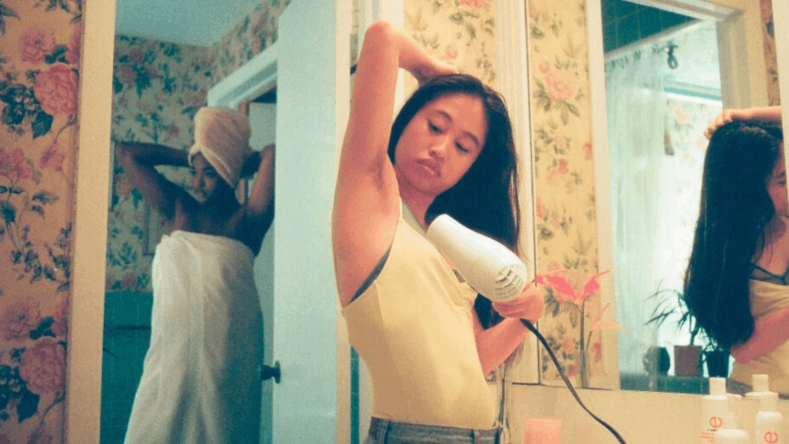 A woman wearing a mustard-colored shirt has her arm lifted up while she blow dries her underarm hair.