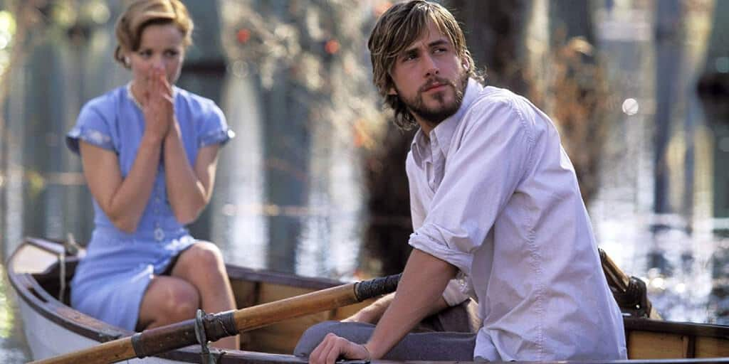 Actors Rachel McAdams and Ryan Gosling in The Notebook. The two characters are in a boat. She is wearing a blue dress and he is wearing a white shirt and grey pants.