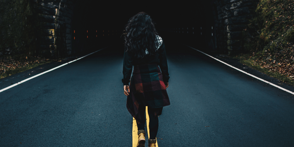 Woman walks into a tunnel. / Photo by Brittani Burns on Unsplash