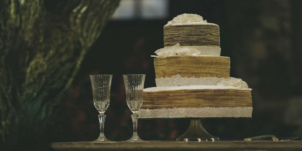 [Image Description: Two wine chutes next to a three-tiered white and brown wedding cake, on a wooden table] via Tikkho Miaciel on Unsplash