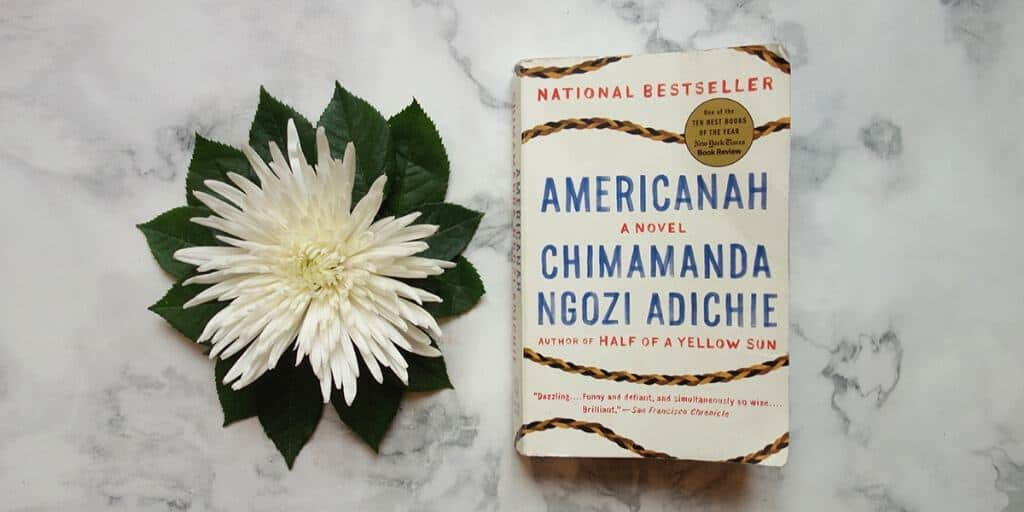 An open flower lies next to the book Americanah on a white marble surface.