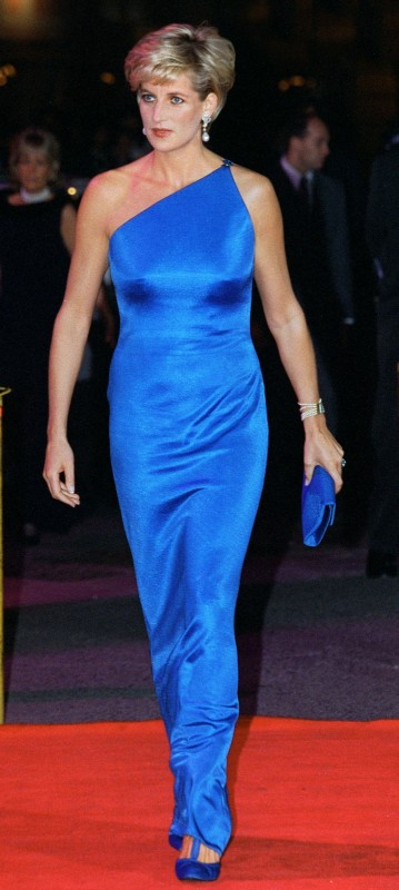 Princess Diana, a white woman with blonde hair, wearing a blue one-shoulder gown on a red carpet. Via Getty Images.