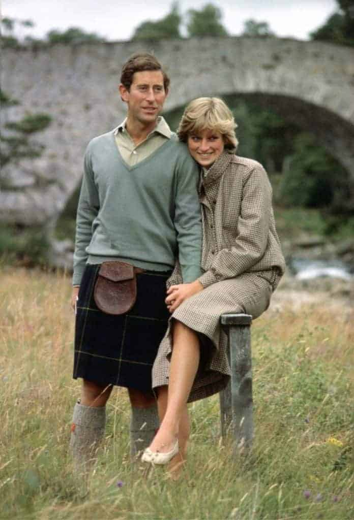 Princess Diana, a white woman with short blonde hair, is wearing a tweed jacket and skirt. She is sitting next to Prince Charles, a tall white man with brown hair, wearing a teal crew-neck sweater and black kilt. Via Getty Images.
