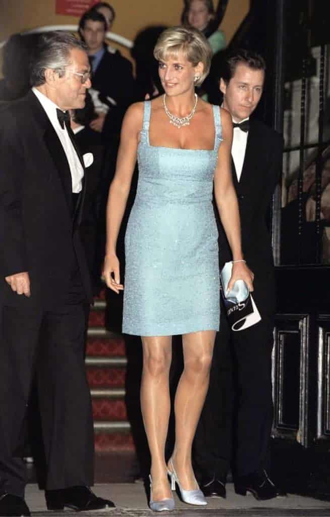 Princess Diana, a white woman with blonde hair, wearing a fitted teal embellished dress and smiling. Via Getty Images.