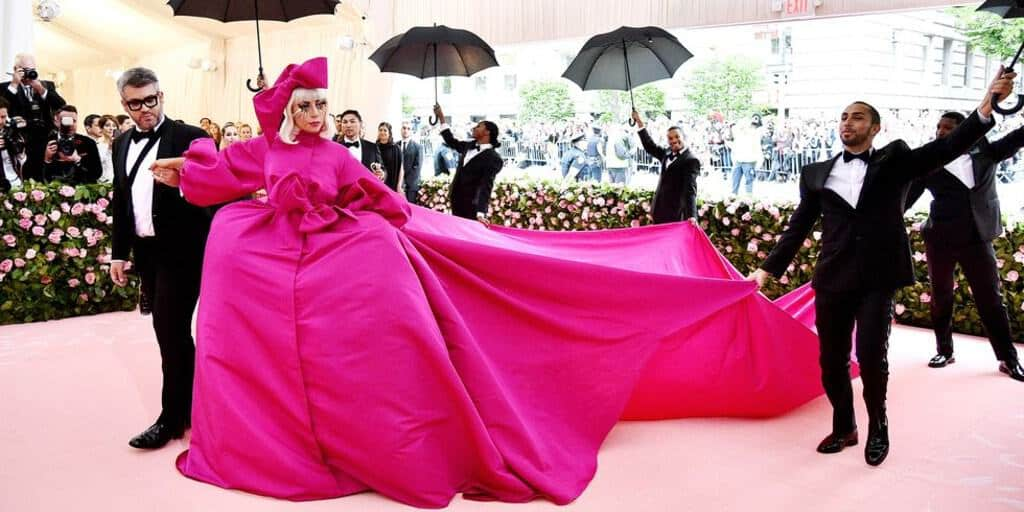 Lady Gaga, a white woman with short blonde hair, is standing on a pink carpet wearing a large bright pink dress with a matching large ribbon. Via Getty Images.