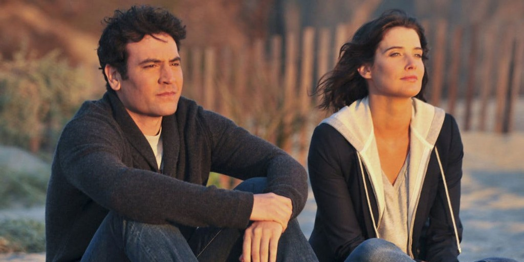 A still image of How I Met Your Mother's Ted and Robin - both white and dark-haired - sitting on the beach looking out to the sea.