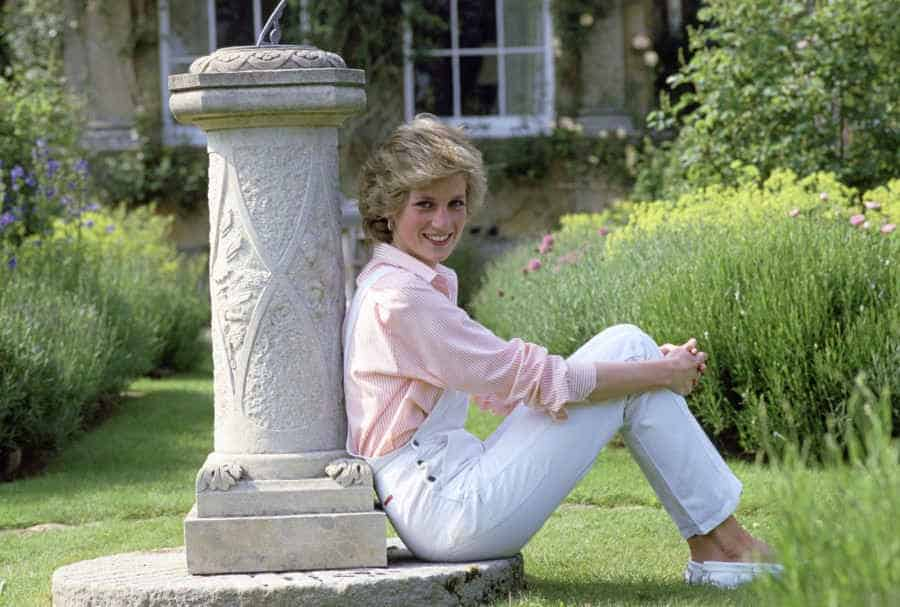 Princess Diana, a white woman with blonde hair is sitting on the ground wearing while wearing a pink striped shirt and white overalls and white boat shoes. She is smiling into the camera. Via Getty Images.