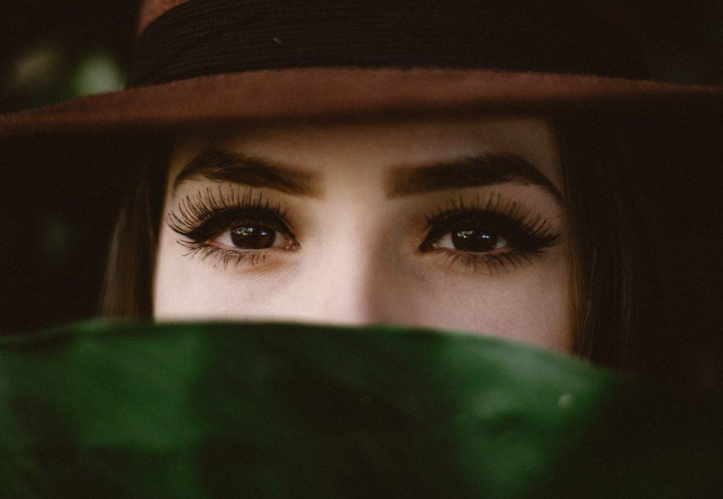 A woman with brown eyes looking into the camera. Via Unsplash