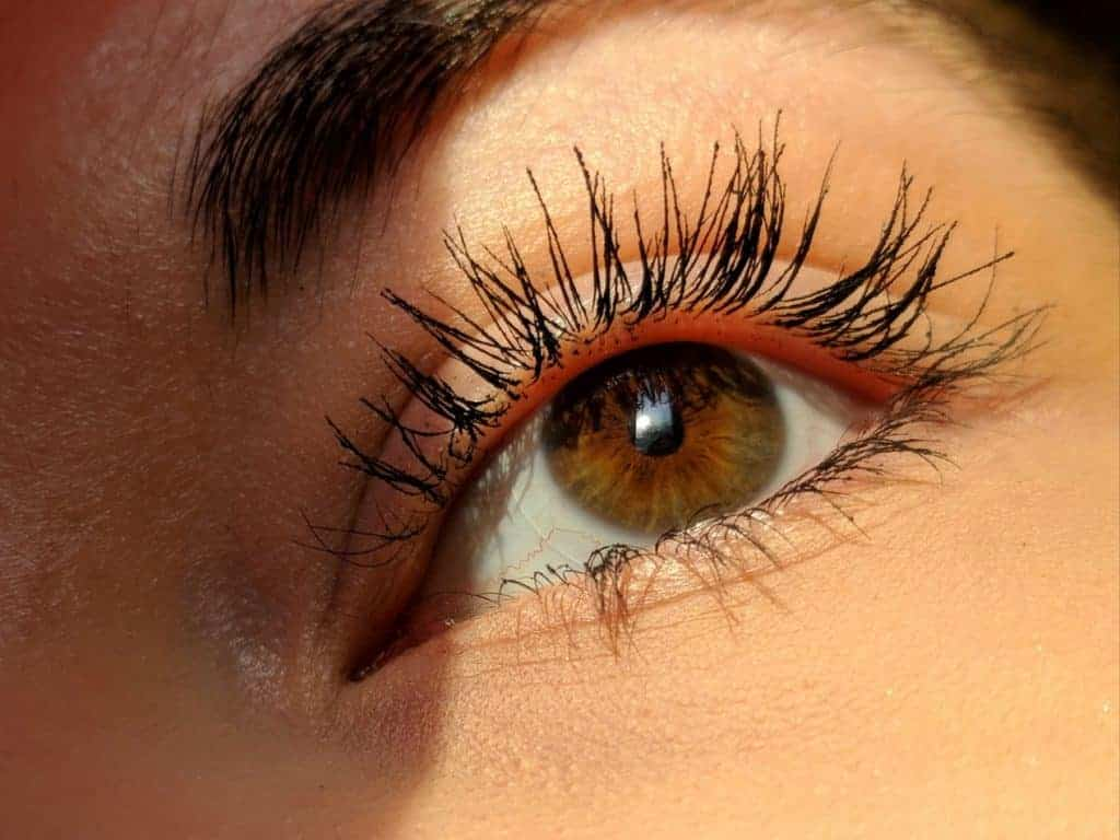 A woman's left eye, which is brown in colour with long, dark lashes.