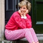 Princess Diana sitting in pink gingham cropped pants and a pink sweatshirt. She is smiling into the distance. Via Getty Images.