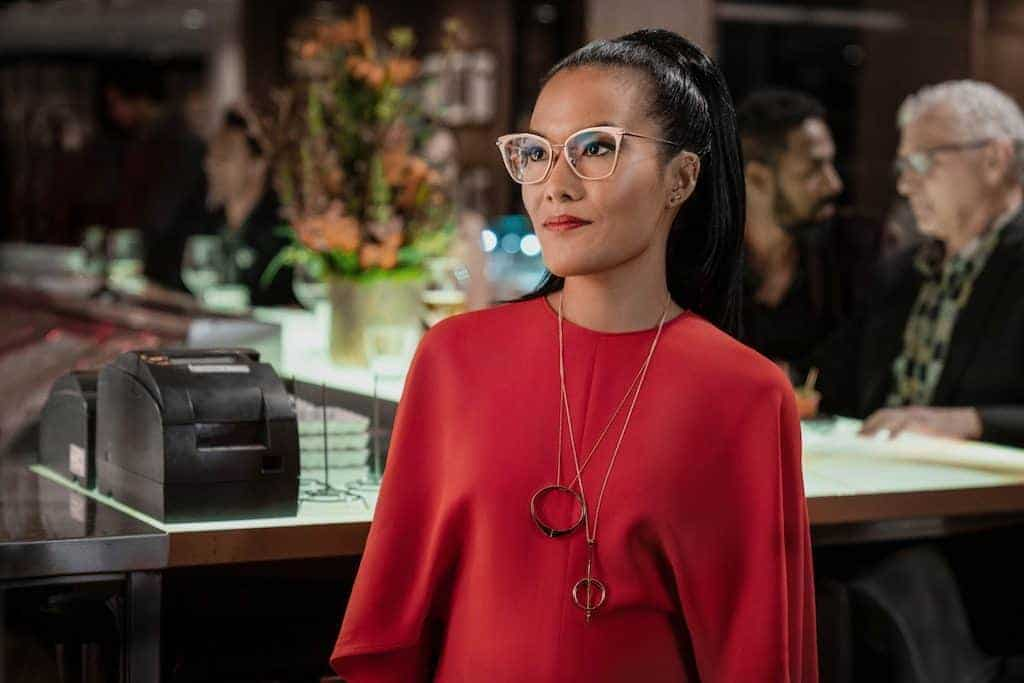 The character Sasha Tran played by Ali Wong stands facing the camera, wearing a full-sleeved red dress and a silver necklace.