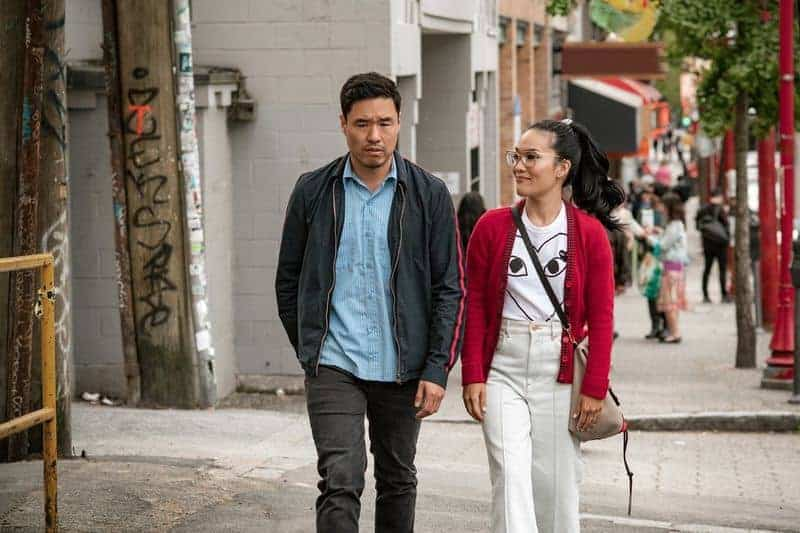 Sasha Tran, played by Ali Wong, and Marcus Kim, played by Randall Park, walk on a street side by side. Sasha is wearing white jeans, a white graphic shirt and a red cardigan, while Marcus wears a light blue shirt and a dark gray jacket.