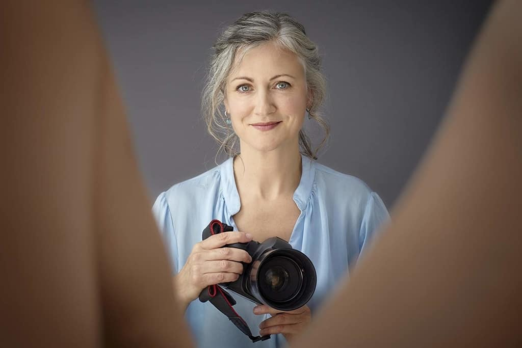 image description: a woman is smiling while holding a camera between an open pair of legs