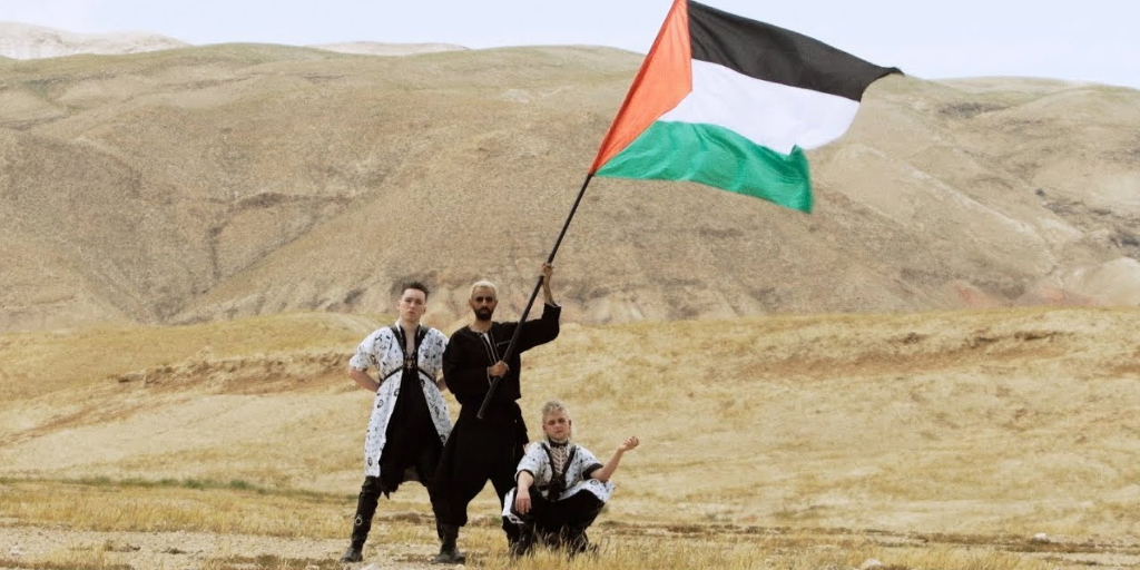 Bashar Murad and Hatari holding up a Palestinian flag in the desert in the music video for KLEFI / SAMED (صامد)