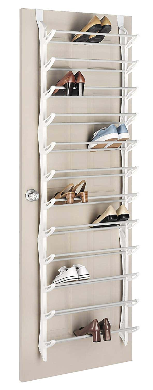A shoe rack hanging over a door holding a few pairs of shoes.