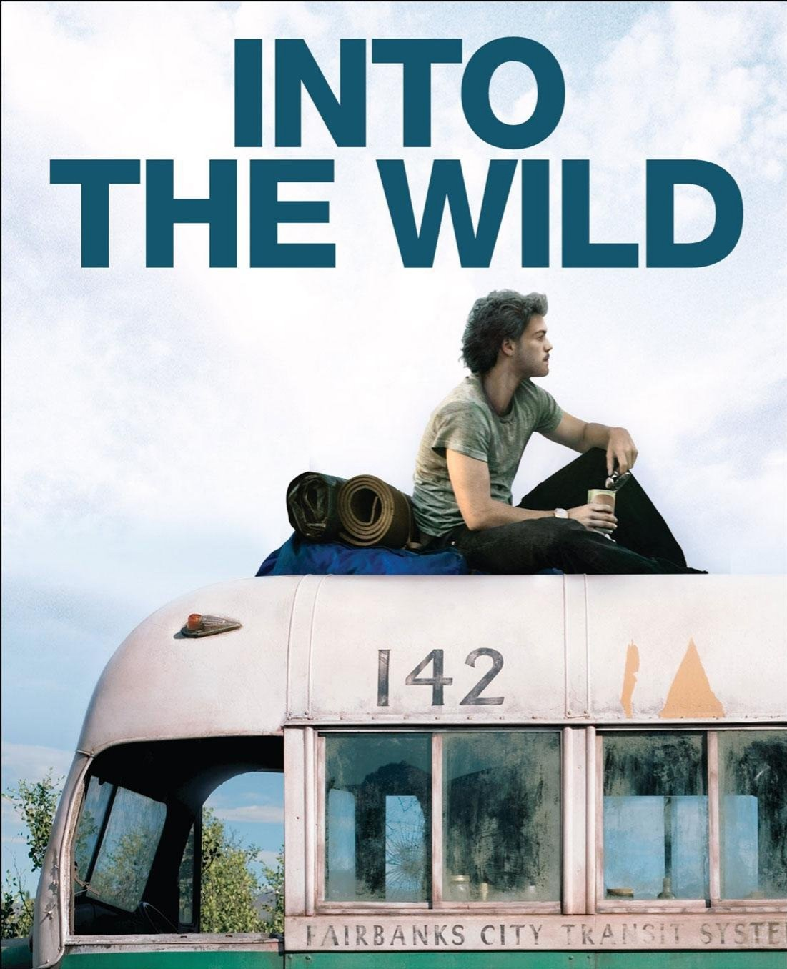 "A white man with short brown hair is sitting on a van looking into the distance under the words ""Into the Wild""."