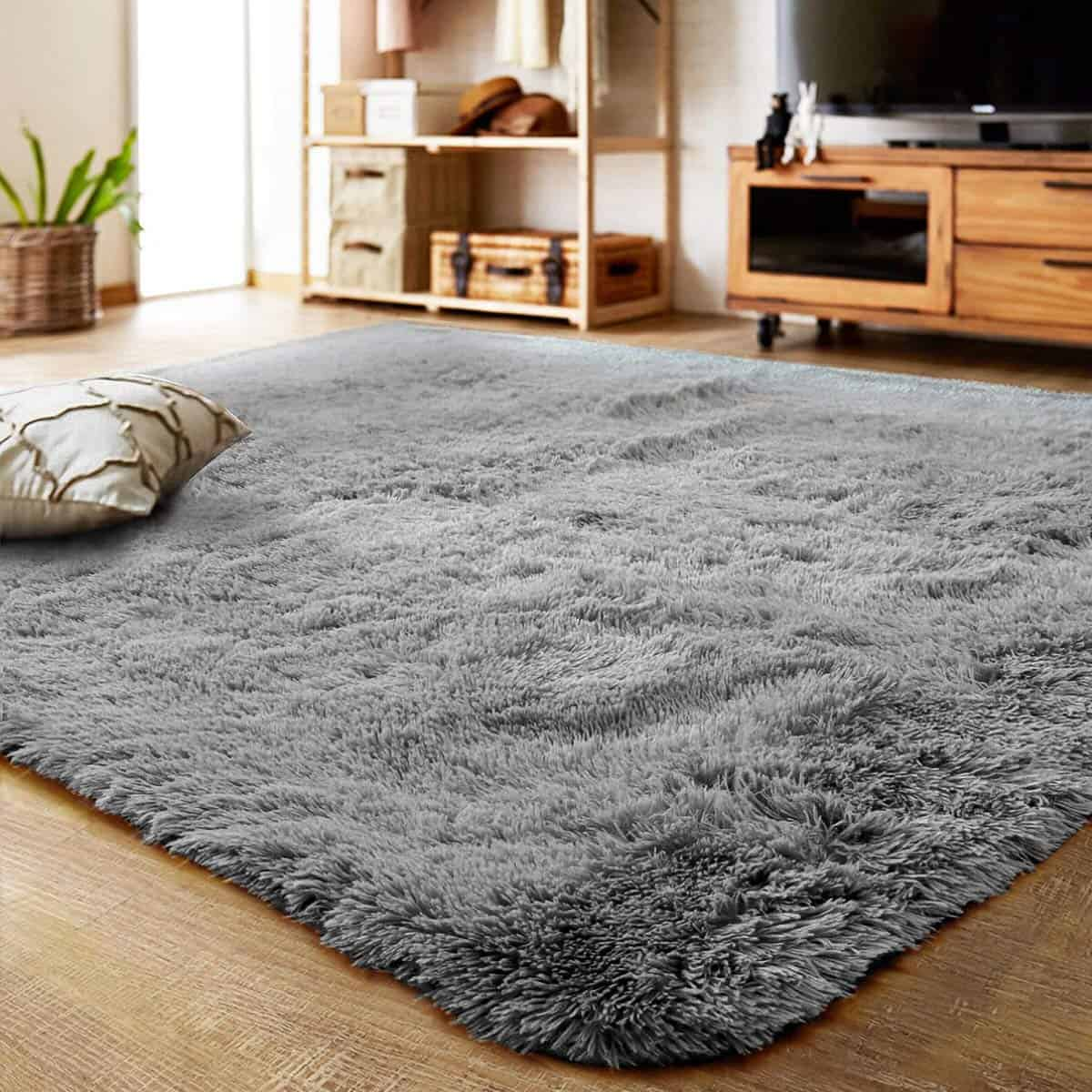 A soft, gray rug is spread across a hardwood floor.