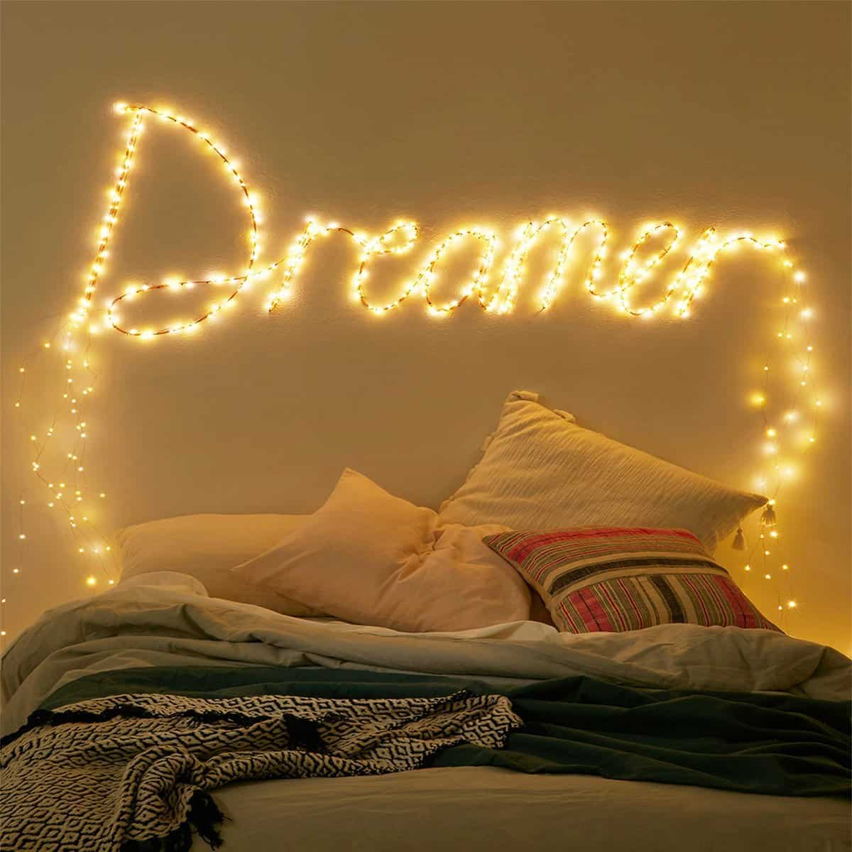 The word 'Dreamer' is spelled out in fairy lights over a cosy bed in a dimly, yellow-lit room.