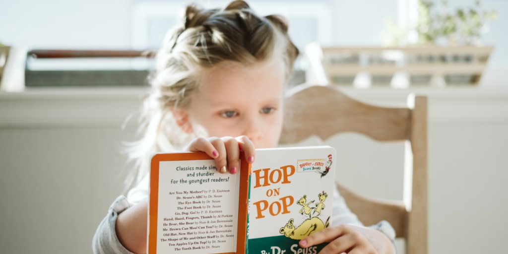 A young white girl with blonde braided hair reads a Dr. Seuss book, the camera focuses on the book cover
