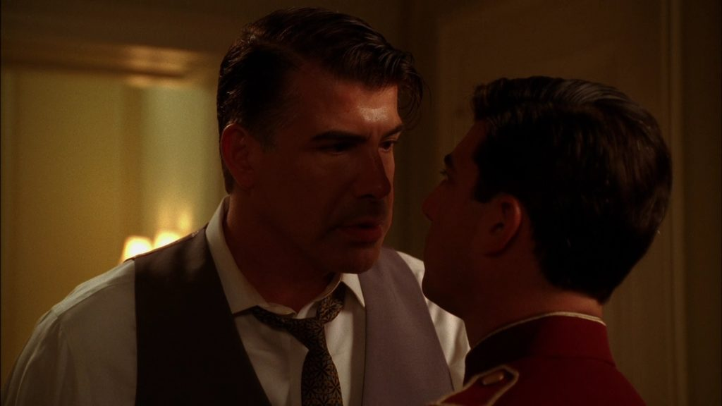 Two dark-haired white men - one in a suit, the other in a red bellhop uniform - are staring each other down.