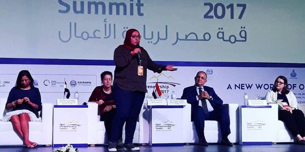 Doaa Aref, a brown woman in blue jeans, a dark top and a hijab is on stage, giving a presentation. Behind her sits a panel three women and one man.