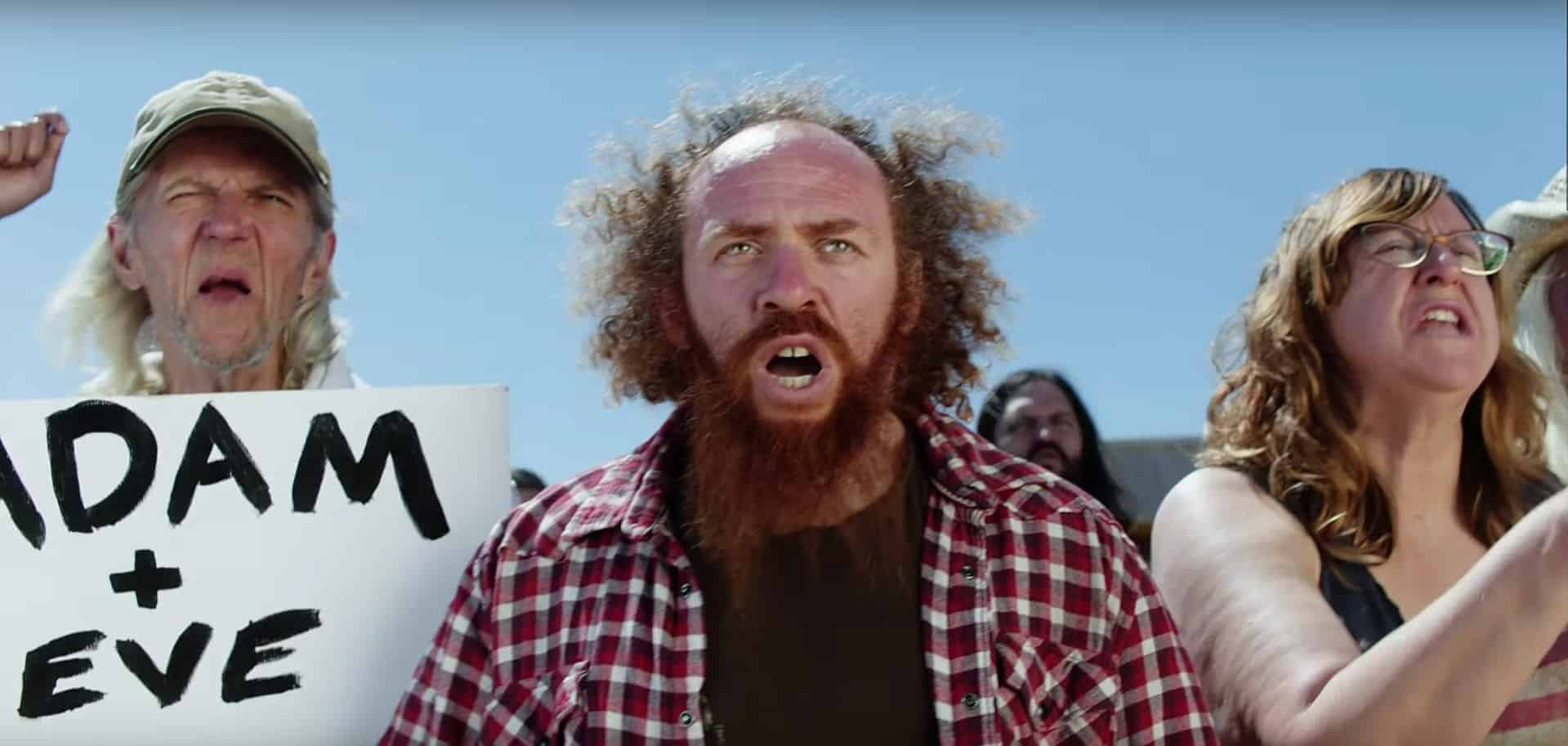 """Still from Taylor Swift's """"You Need to Calm Down"""" video. A red-haired man with a beard wearing a red plaid shirt over a black t-shirt takes part in an anti-LGBTQIA+ protest. Behind him, similarly dressed protesters hold signs and yell."""