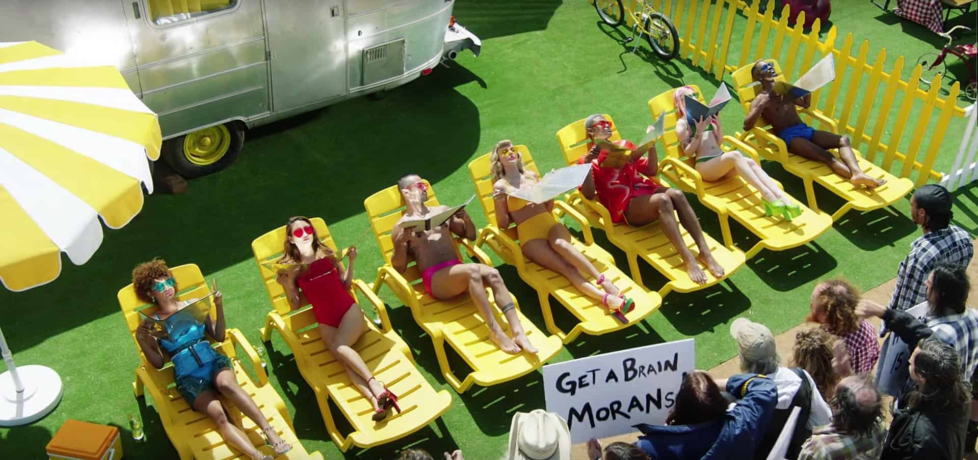 """Still from Taylor Swift's """"You Need To Calm Down"""" music video. Swift and friends lay in a line of yellow beach chairs outside a trailer suntanning with reflectors while anti-LGBTQIA+ protesters gathers parallel to them, yelling."""