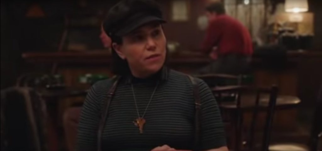A woman in a blue striped shirt, suspenders, and a newboy cap is seated in a dark restaurant.