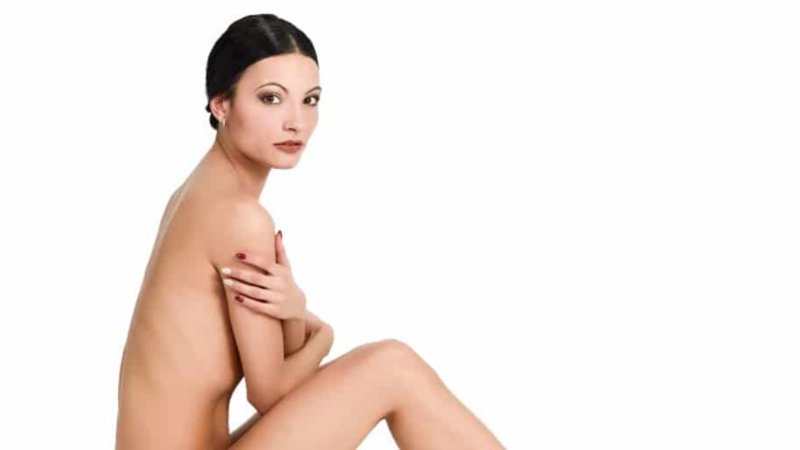 A black-haired woman sits nude against a white backdrop. Her arms and legs used to cover herself up as she stares stoically into the camera.