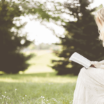 A profile shot of a white, blonde woman sitting on a rock in a green field. Her head is titled down to the book in her hands. She's dressed in a red velvet top and a white skirt.