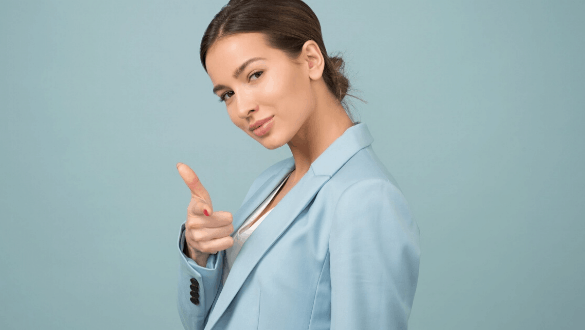[Image description: A brown-haired woman in a baby blue blazer is half-turned and holding up a finger gun. She has a playful smile on her lips.] Via Moose Photos on Pexels