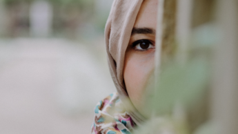 [Image description: Woman looks out from a wall where most of her face is covered.] Photo by Mohammed Hassan on Unsplash