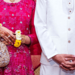 [Image description: Woman and man dressed in bright wedding clothes.] Photo by Khadija Yousaf on Unsplash