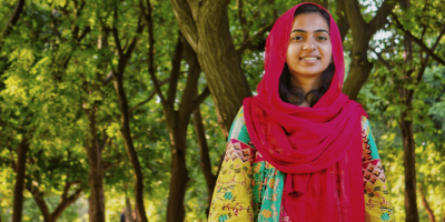 [Image description: Girl stands in a scarf under a tree, smiling.] Photo by Khadija Yousaf on Unsplash