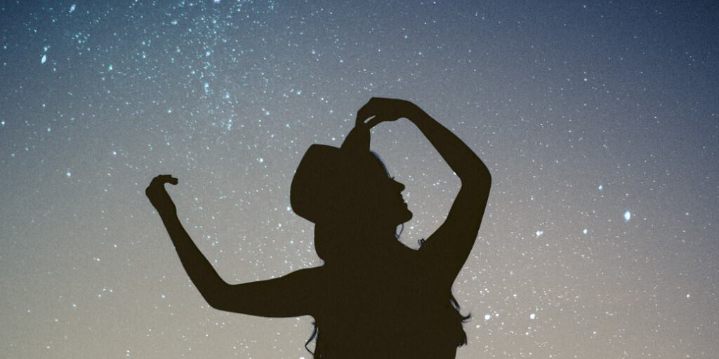 A woman is silhouetted with her arms raised against a blue starry sky, her face and body thrown into shadow.