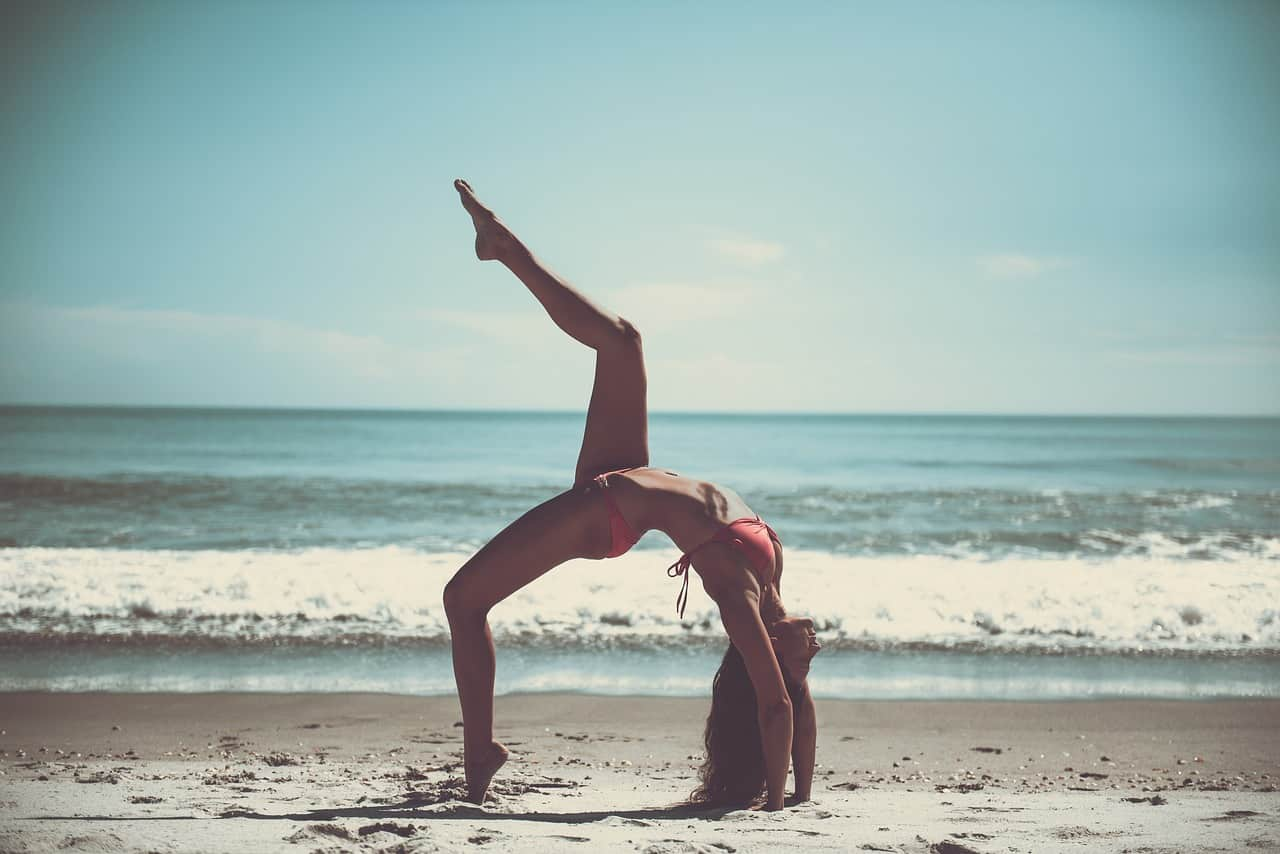 Woman attempting a handstand on a beach whilst wearing a bikini.