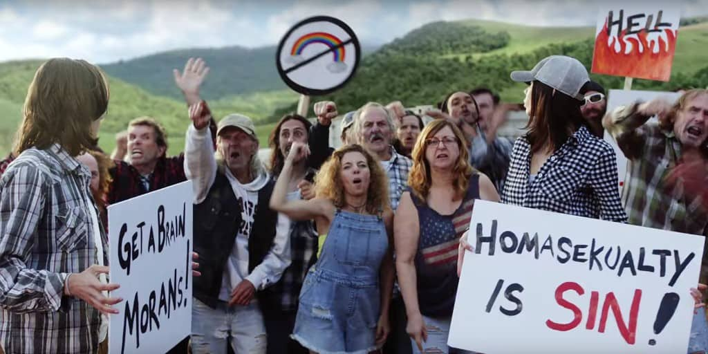 "Still from Taylor Swift's ""You Need To Calm Down"" music video. A crowd of anti-LGBTQIA+ protesters jeer. Their signs read ""Get a Brain Morans"" and ""Homasekualty is sin!"""