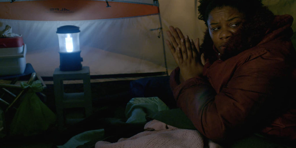 Cindy, a black woman, sits in a tent, heating her hands up with one lone white light on the side